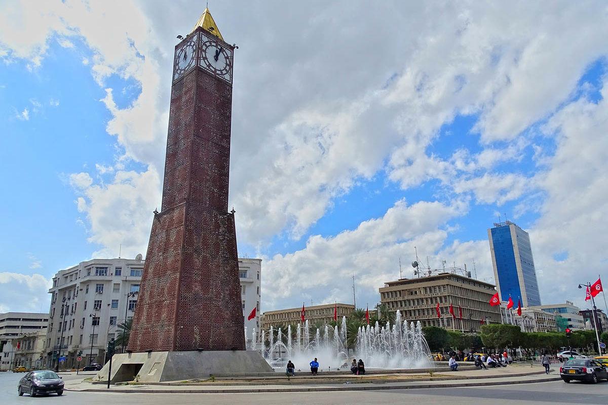 Ein großer Uhrenturm auf einem zentralen Platz in Tunis. Tunesische Flaggen im Halbrund im Hintergrund