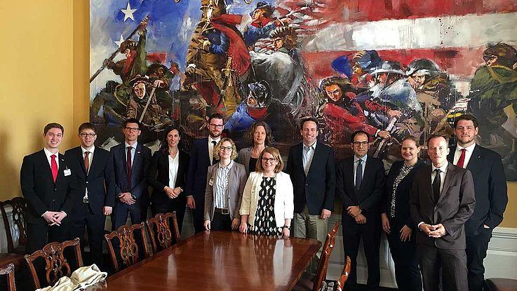 Gruppenbild mit Delegierten vor einem überdimensionalen Ölbild mit höchst amerikanischen Motiven.