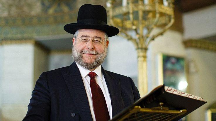 Freundliche blickender Rabbiner mit Hut, Krawatte und kurzem Vollbart in einer Synagoge