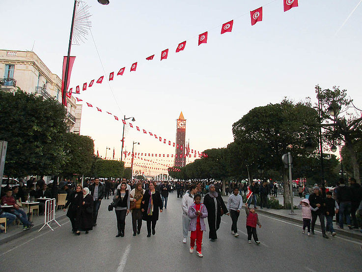 Eine mit Flaggen geschmückte Hauptstadtstraße, auf der Menschen in kleinen Grüppchen auf die Kamera zuschlendern. Im Hintergrund ein von der letzten Abendsonne beschienener Turm.