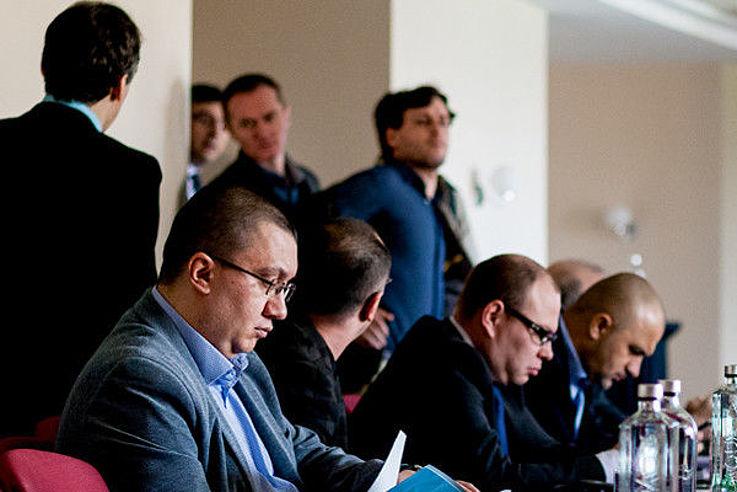 Blick auf die Teilnehmer des Seminars, die teils sitzen oder im Hintergrund stehen und sich unterhalten