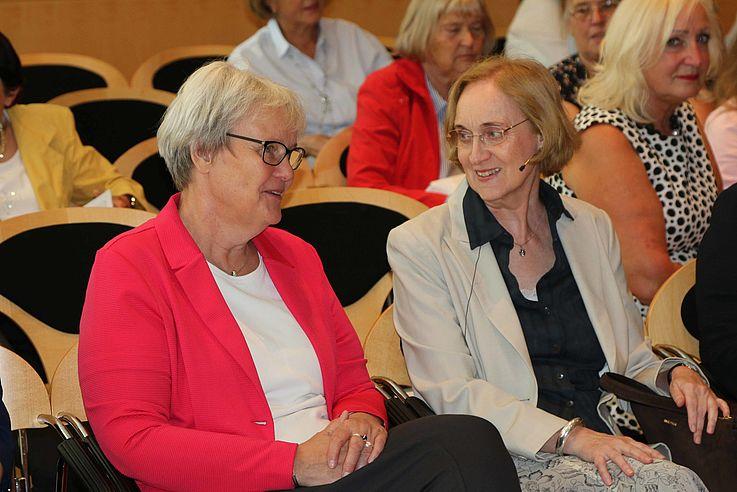 Zwei Damen in der ersten Reihe des Plenums unterhalten sich.