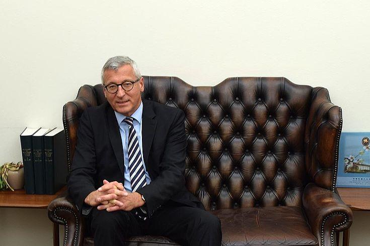 Freundlicher Herr im Anzug und mit Brille sitzt auf einem Sofa, die Hände gefaltet.