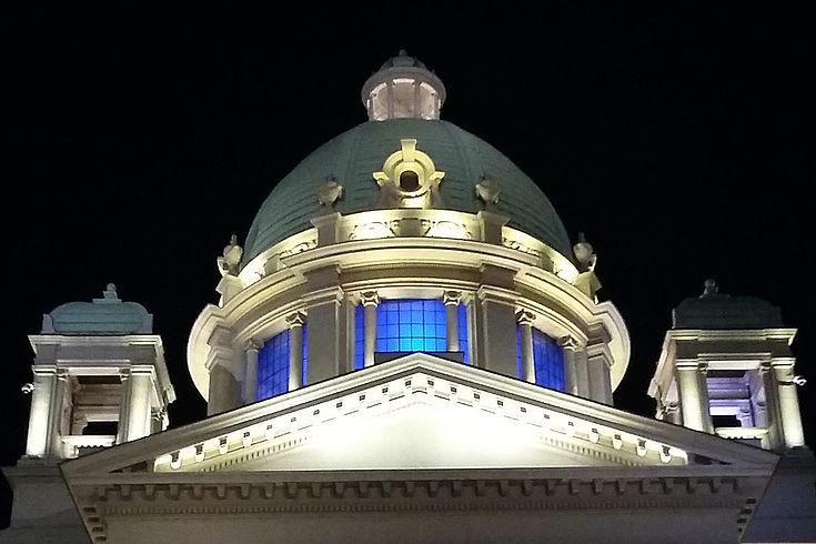 Teilansicht des Parlamentsgebäudes in Belgrad bei Nacht mit erleuchteten Fenstern in der Kuppel