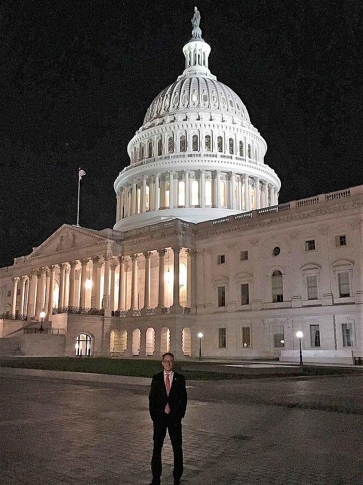 Forstner steht in elegantem Anzug breitbeinig vor dem nur halb erleuchteten Kapitolsgebäude. Es ist Nacht. Die Kuppel hebt sich vor dem Nachthimmel ab.