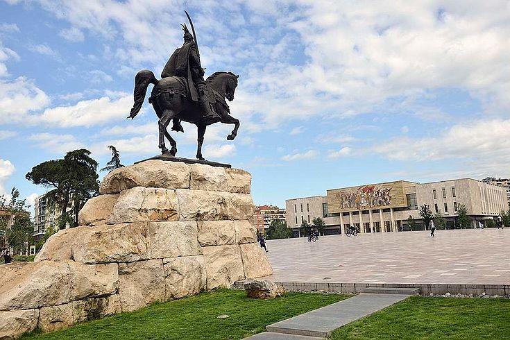 Ein Reiterstandbild auf einem steinernen Podest, das auf das albanische Nationalmuseum zeigt