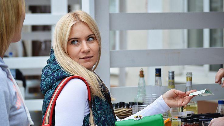 Junge Frau bezahlt gerade eine Ware mit einem Geldschein.