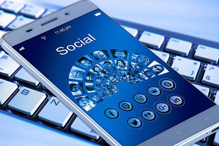 """Themenbild eines Handys auf einer Tastatur. Auf dem Bildschirm steht: """"Sozial"""""""
