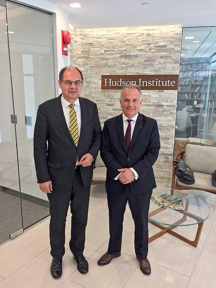 Die beiden Herren vor einer an die Backsteinwand geschraubten Plakette auf der steht: Hudson Institute