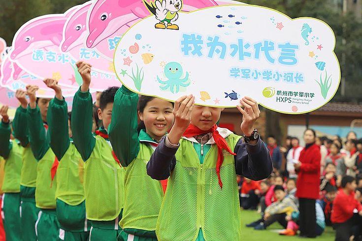 Chinesische Schüler in grüner Kleidung halten selbstgemachte Plakate zum Schutz des Wassers in den Händen