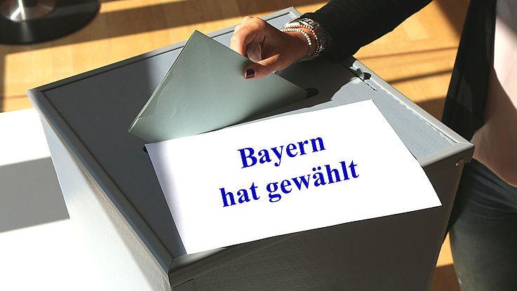 Es wird ein Wahlschein in eine graue Wahlurne eingeworfen