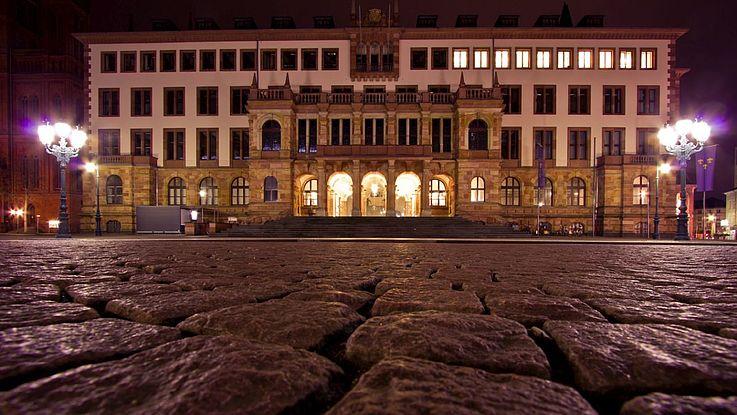Modernes, eckiges Rathaus bei Nacht. Im Vordergrund das Kopfsteinpflaster, hinten das Rathausgebäude.