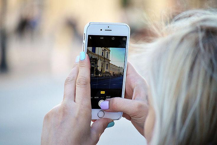 Frau hält Handy vor ein Gebäude und schießt ein Foto. Es ist auf dem Bildschirm abgebildet.