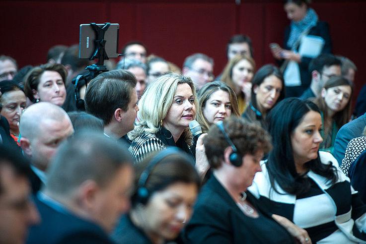 Sehr distinguiert anzusehende Frau im Plenum stellt eine Frage.