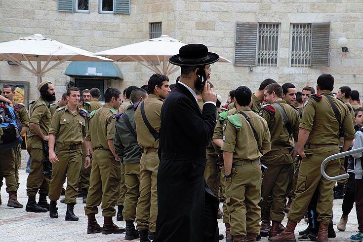 Orthodoxer Jude mit Handy am Ohr geht an einer Gruppe Soldaten vorbei.
