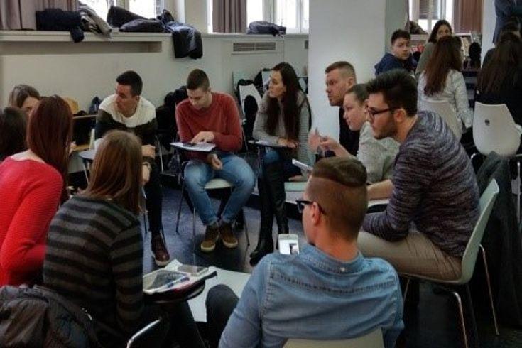 Eine Gruppe junger Menschen sitzt in einem Stuhlkreis zusammen. Ein Teil der Gruppe diskutiert, ein anderer Teil hört interessiert zu.