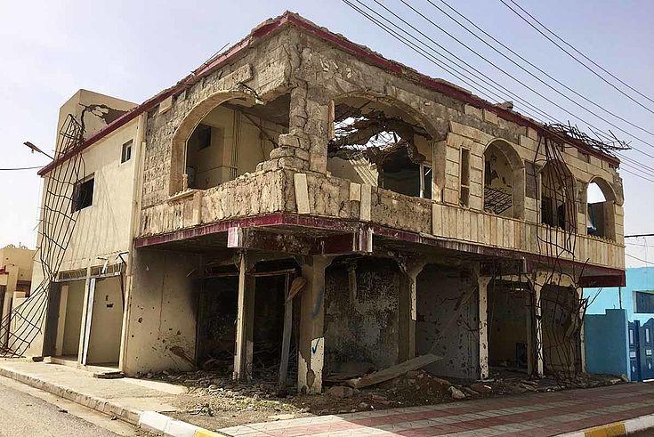 Ein zerstörtes Wohnhaus an einer Straße in Telskuf. Leere Fensterhöhlen, die Innenwände tragen die Struktur, die äußeren Wände fehlen.