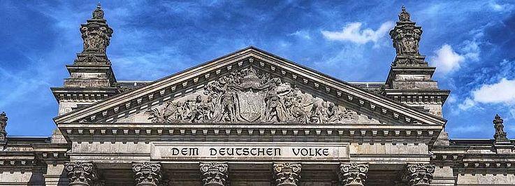Der Bundestag von vorne: Säulen tragen ein flaches, spitzes Dach mit der Aufschrift: Dem Deutschen Volke
