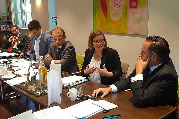 Konferenztisch mit mehreren Experten und einer Expertin, die engagiert diskutiert