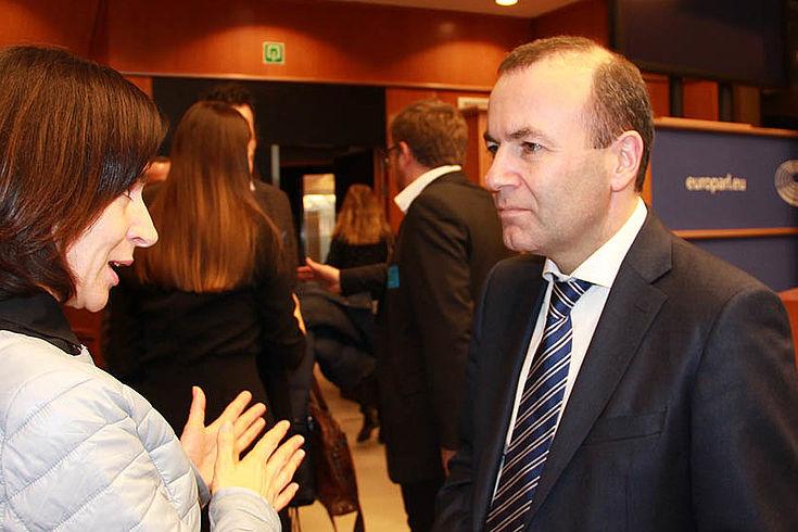 Manfred Weber wird von einer Frau gerade etwas gefragt. Er blickt konzentriert bis grimmig.
