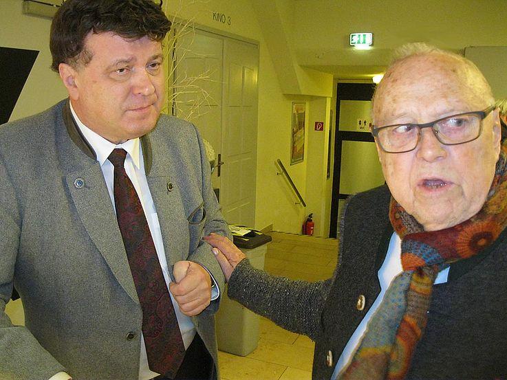 Vilsmaier dreht sich nach rechts und fasst den links neben ihm stehenden Arthur Kolbe am Arm, als wolle er ihn auf etwas hinweisen.
