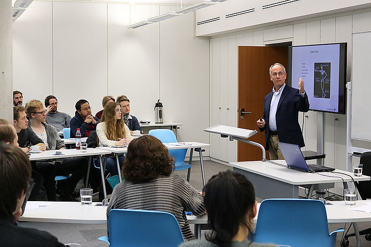 Prof. Reinie doziert vor einer kleinen Gruppe junger Studenten. Hinter ihm ein Whiteboard mit Schaubildern.