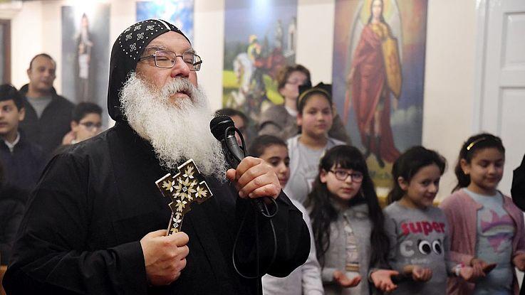 Bischof Damian in der langen Robe der Kopten mit orthodox verziertem Kreuz in der einen und Mikrophon in der anderen Hand, betet in einer Kirche vor Gläubigen.