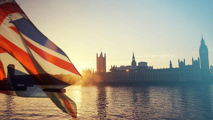 Blick auf Westminster. Im Vordergrund weht ein Union Jack.