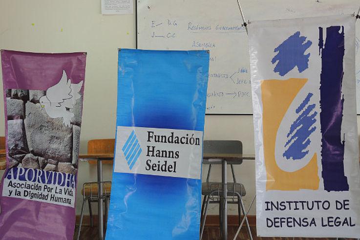 Für die Rechte indigener Völker: Foto mit insgesamt drei Bannern von APORVIDHA, IDL und HSS bei einem Seminar in Cusco