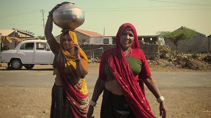 Zwei Frauen mit Krügen voller Wasser auf einer staubigen Straße