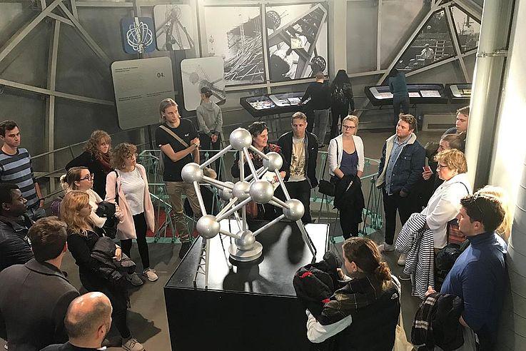 Ein Besuch in Brüssel ohne Abstecher ins Atomium ist wie München ohne Oktoberfest. Das Wahrzeichen der Stadt wurde zur Weltausstellung 1958 – damals in einer aufkommenden Euphorie der zivilen Nuklear-Nutzung – als Blick in das kubisch raumzentrierte Kristallgitter von Eisen (165-milliardenfach vergrößert) errichtet. Die neun Kugeln haben einen Durchmesser von je 18 Metern, das ganze Atomium ist 102 Meter hoch. Ein Aufzug bringt die Besucher in die oberste Kugel, Treppen führend in die anderen begehbaren Kugeln. Die Röhren zwischen den Kugelatomen symbolisieren keinesfalls fixe Bindungen des Eisens. Sie entsprechen aber wie im makroskopischen Europa – von der heutigen EU ahnte man 1958 ja noch nichts – dem realen Beziehungsgeflecht: Nimmt man einen Stab oder eine Kugel weg, so käme das Ganze ziemlich in Schieflage, wenn nicht gar zum Einsturz.