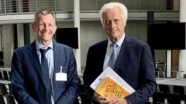 Cilliers und Raumsauer in einem hohen Raum mit Säulen im Hintergrund. Ramsauer hält das Buch in der Hand. Beide lächeln.