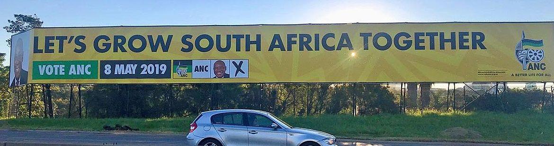 30 Meter breites Wahlplakat, an dem gerade ein Auto vorbeifährt.