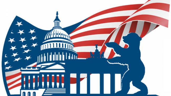 Logo: mit dem US-Capitol, dem Brandenburger Tor und dem Berliner Bären. Im Hintergrund die US-Flagge