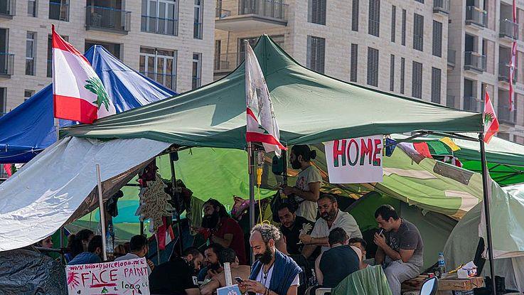 """Zelte auf einer Straße in Beitrut. Wimpel und Spruchbänder, auf einem steht """"home""""."""