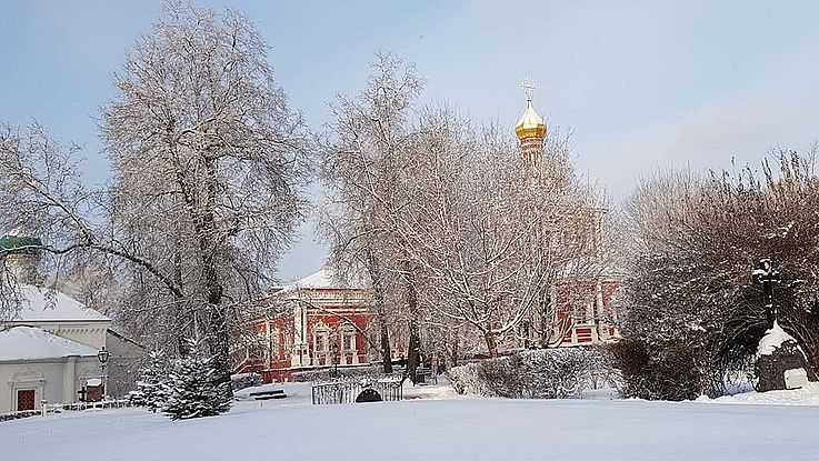 Ein russisches Idyll. Der Zwiebelturm eines russischen Klosters ragt im Hintergrund hinter verschneiten Baumwipfeln in den Himmel.