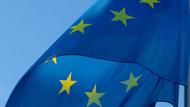 Europaflagge weht vor wolkenfreiem Himmel