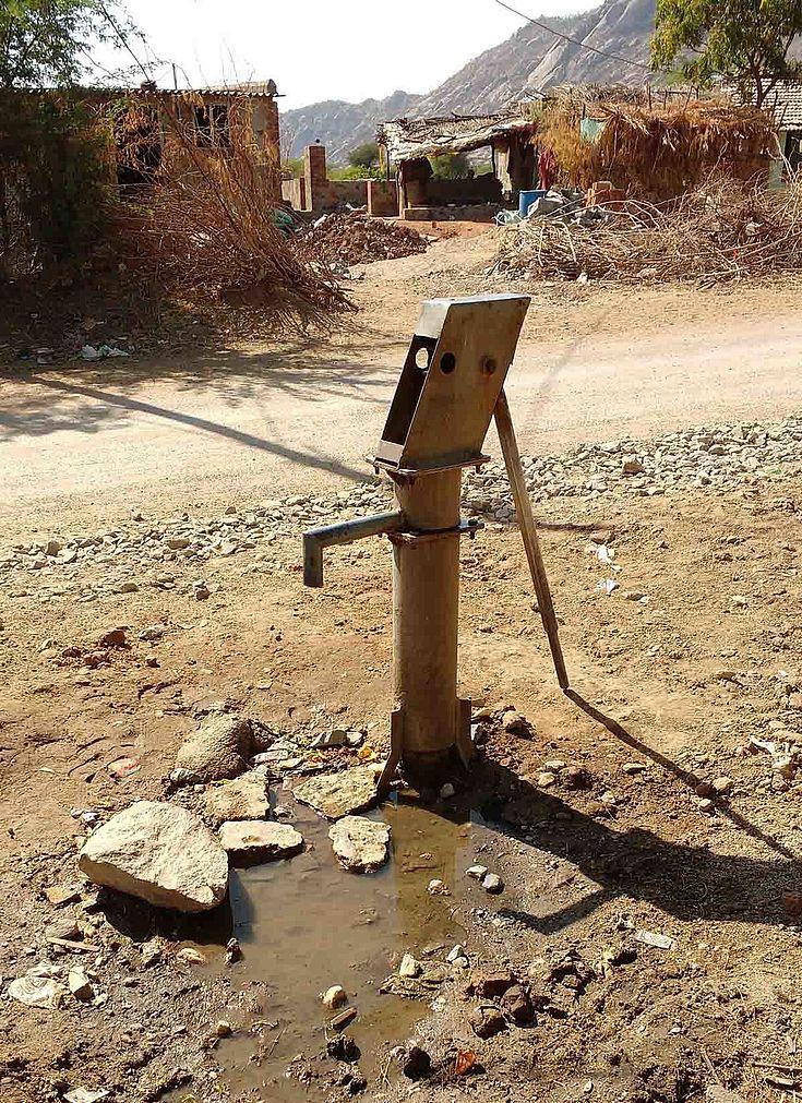 Handpumpe auf einem Dorfplatz. Etwas Wasser um die Stelle, wo sie aus dem Boden kommt.