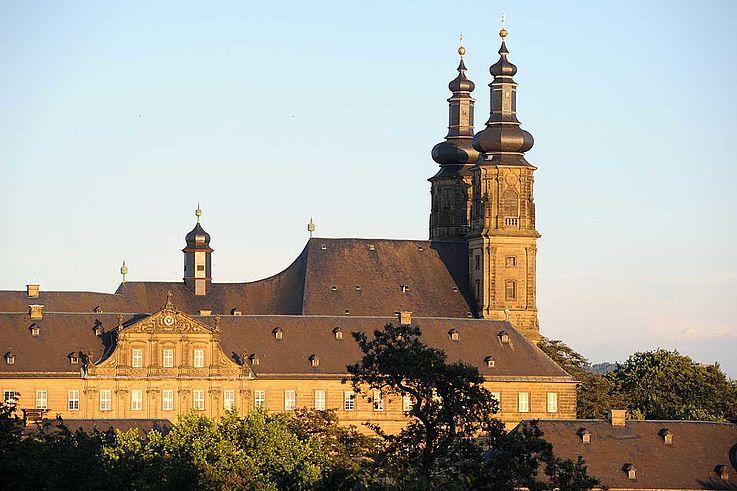 Klostergebäude mit hohen Türmen, umwachsen von kleineren Bäumen vor einem weiten Horizont.