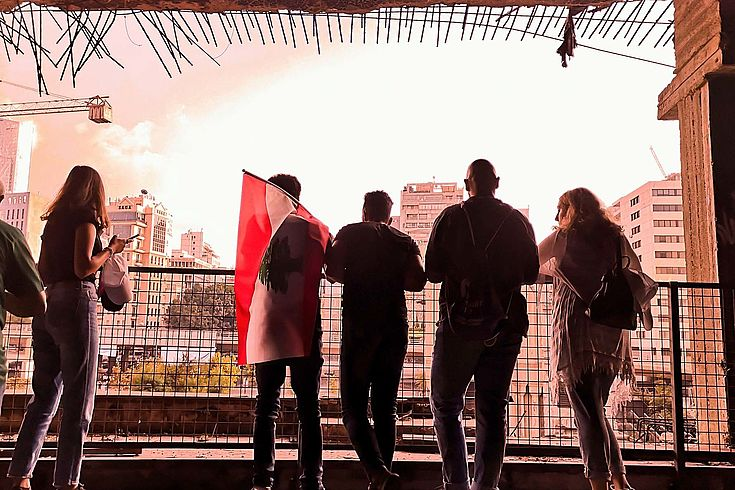 Vier Menschen, einer davon mit der libanesischen Flagge stehen auf einem Balkon in einem zerstörten Gebäude und beobachten die Situation auf der Straße