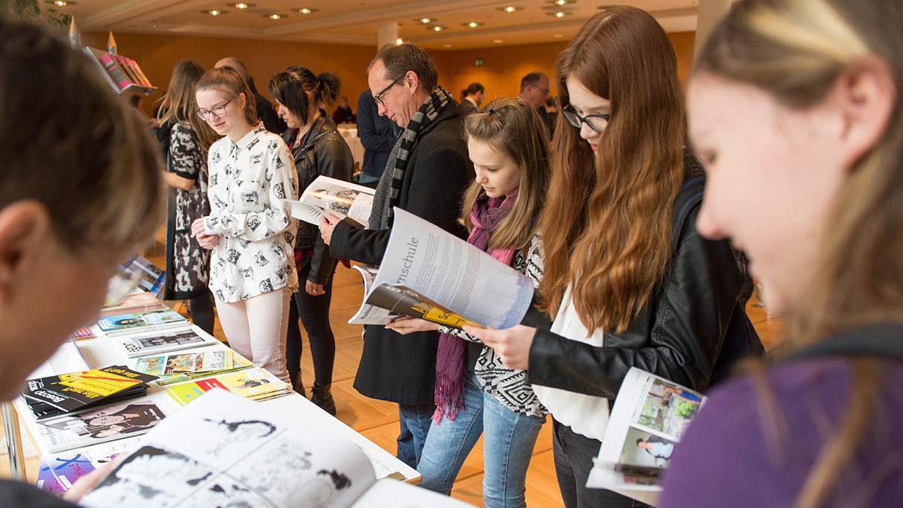 Nachwuchsjournalisten lesen am Zeitungsstand, was die anderen Schülerzeitungen zu bieten haben. Interessiert, amüsiert, konzentriert