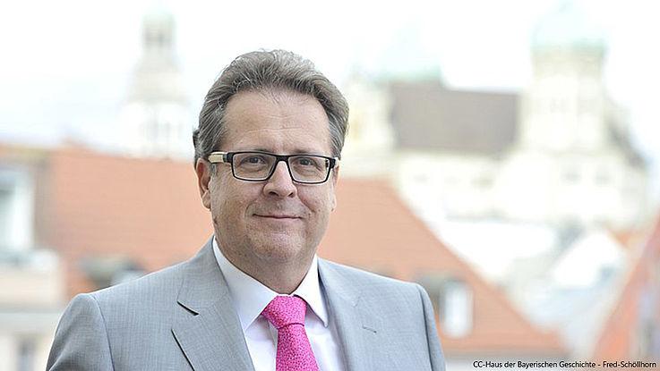 Loibl, ein freundlich wirkender Mann mit Brille und lichter werdendem Haar vor der Kulisse von Regensburg