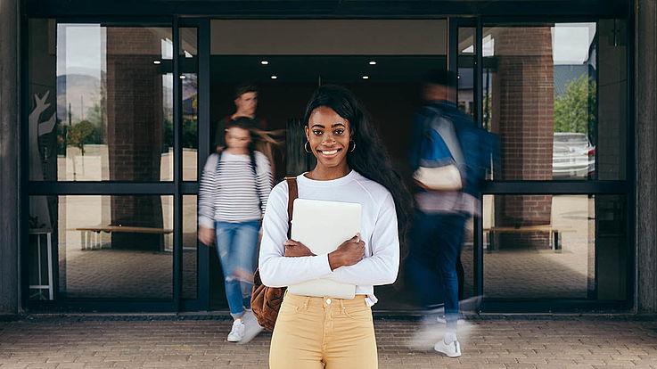 Junge Frau vor den offenen Türen einer Schule