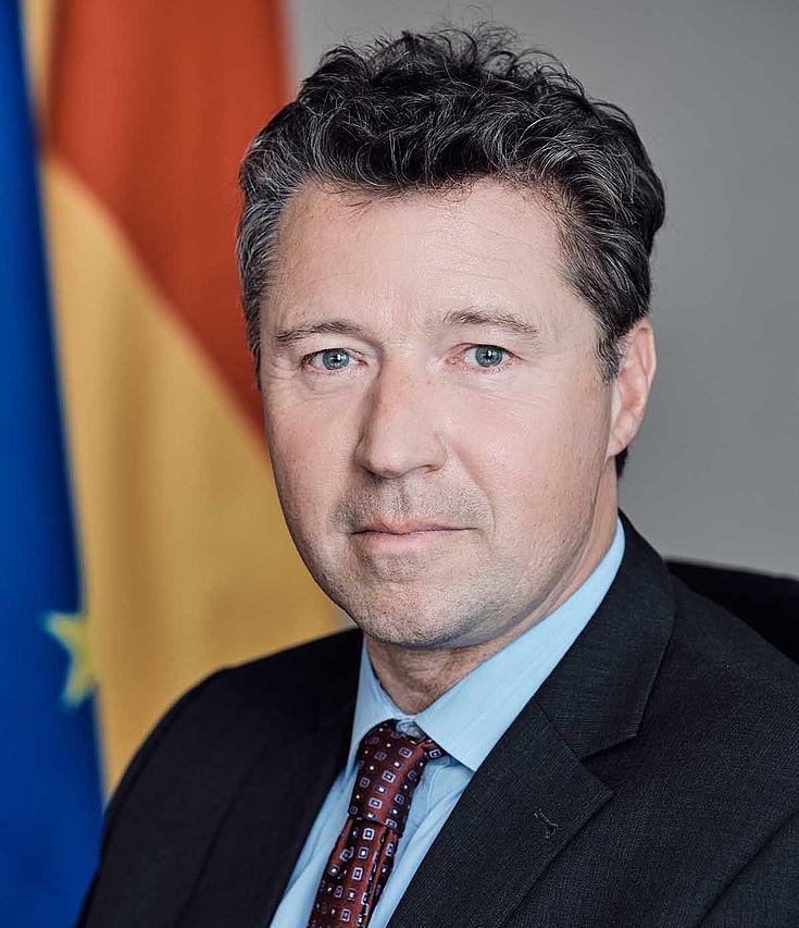 Herr Geyr blickt ernst in die Kamera. Im Hintergrund die Deutschland und Europafahne