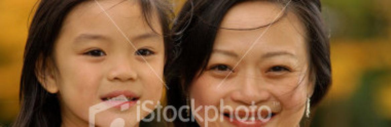 Lächelnde Frau hält lächelndes Mädchen auf dem Arm