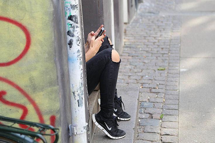 Die Beine eines jungen Menschens mit zerrissener Hose ragen aus einer Einbuchtung in einer Betonstruktur. Das Handy in der Hand ist auch zu sehen. Graffiti, Schmutz, Verwarlosung.