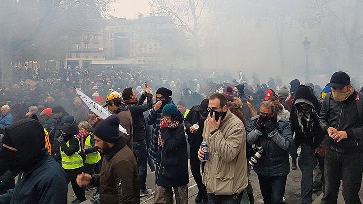 Tränengasschwaden liegen in der Luft. Die Menschen halten sich Schals und Tücher vor die Münder.