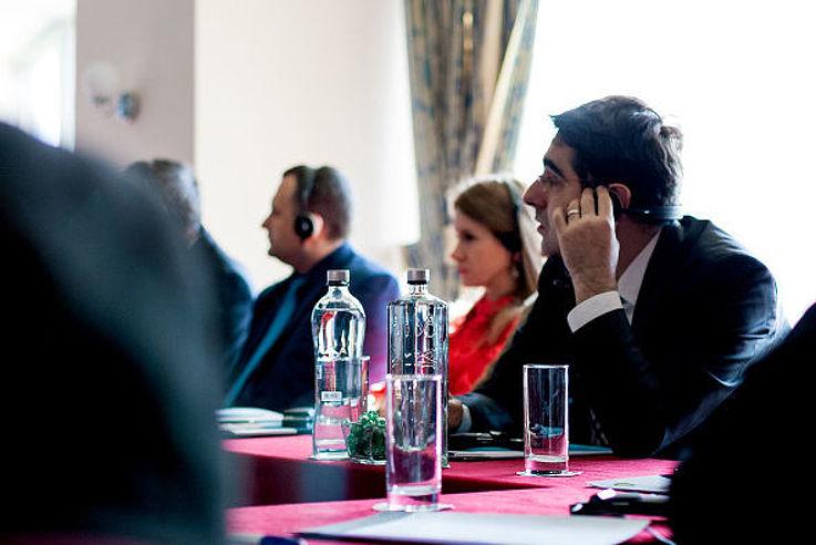 Blick auf aufmerksame Zuhörer, die an einem Konferenztisch sitzen.