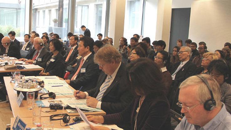 Blick auf Konferenztische und einen Teil der Teilnehmer des Forums