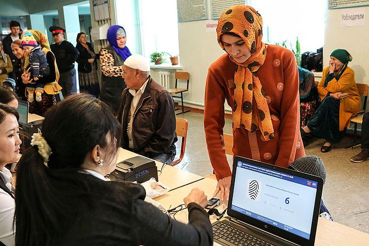 In einem Wahllokal wird eine Wählerin im traditionellen Gewand biometrisch erfasst